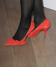 Anne Hathaway paired red suede pumps with black tights.