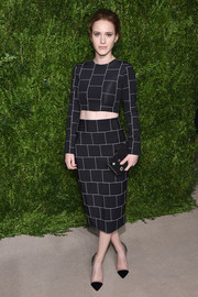 Rachel Brosnahan accessorized with a beaded black clutch for a touch of classic elegance.