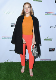 Underneath her coat, Jane Levy wore a bright orange knit top.