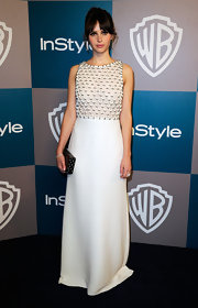 Felicity Jones contrasted her '60s inspired gown with a sleek black box clutch.