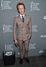 A navy and brown striped tie add a hint of color to Gabriel Mann's tan suit at the Costume Designer's Guild Awards.