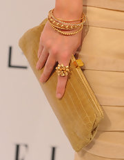Emily wears several gold bracelets, along with one diamond bracelt, to tie together this golden look.