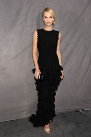 Charlize Theron accented a sumptuous black tiered gown with a matching box clutch.