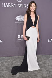 Liu Wen styled her dress with a metallic striped clutch.