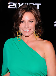 LuAnn de Lesseps medium-length, layered bob was set in waves for the 2(X)ist Spring 2012 presentation. Recreate the look by using a medium-barreled curling iron to curl one-inch sections of hair. Tousle with fingers and mist with Bumble and Bumble Classic Hairspray for strong, yet flexible hold.