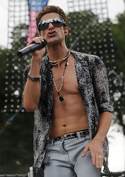 Perry hit the stage at Lollapalooza wearing shield sunglasses and an unbuttoned shirt that showed off his 6-pack and a trio of layered silver necklaces.