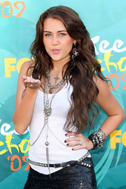 Miley Cyrus paired her sequin mini skirt and white tank top with an arm full of bangle bracelets.