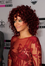 Rihanna debuted deeper red tresses at the American Music Awards. The songstress traded in her long bright red hair for bouncy medium length curls.