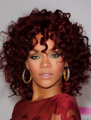 Rihanna paired her deep red ringlet curls with diamond hoop earrings while walking the red carpet at the American Music Awards.