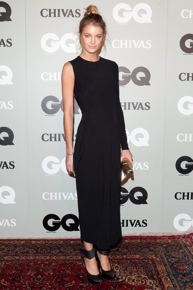 Elyse Taylor paired her minimalist black dress with satin platform pumps with wrap around ankle straps. A messy top knot completes her modern evening look.