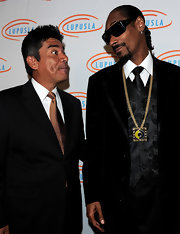 Snoop topped off his tailored suit with a gold record player pendant necklace.