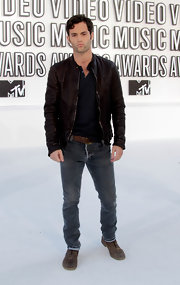 Penn Badgley paired his brown leather jacket with grey henley and denim pants.
