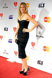 Sheryl topped off her outfit with a pair of sky-high black patent pumps.
