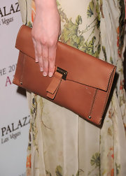 Krysten Ritter paired a romantic floral dress with a leather Jimmy Choo clutch.