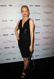 Mena Suvari paired a classic black cocktail dress with strappy satin sandals. The satin material complements the dress' cummerbund.