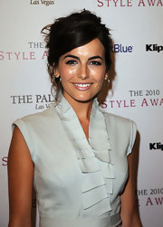 Camilla Belle opted for a messy updo to offset her pleated sleeveless dress.
