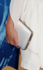 Selena Gomez paired her white dress with a white hard case clutch.