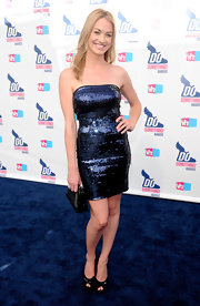 Yvonne wore a shimmering, strapless navy cocktail dress with black peep toe pumps.