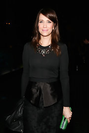 Kristen Wiig added a perfect pop of color to her sleek black ensemble with a glittery green clutch.