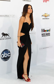 Selena Gomez added a feminine touch to her sultry Dolce & Gabbana dress with red bejeweled bow front sandals.