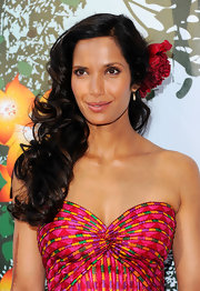 Padma Lakshmi styled her hair in soft side swept curls which she accented with a rose.
