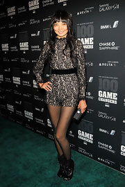 Irina Pantaeva stepped onto the green carpet in a long-sleeved lacy romper and sheer black stockings.