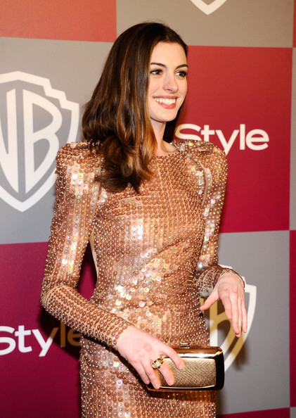 Anne Hathaway accessorized her gorgeous sequined gown with a matching gold box clutch.