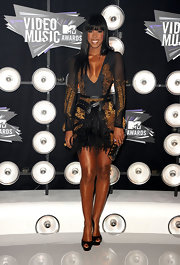 Kelly Rowland was sexy in a feathered dress at the VMAs. Kelly opted for a black dress with a plunging neckline, gold embroidered details and feathered and leather accents.