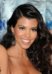 Kourtney Kardashian offset her retro curls with sparkling diamond Starburst earrings.