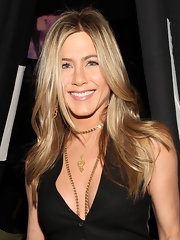 Jennifer Aniston highlighted her plunging neckline with a 19th Century gold chain necklace.