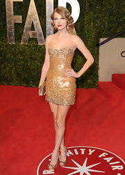 Taylor flaunted her signature style at the Vanity Fair Oscar party in an orange beaded strapless cocktail dress.