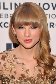 Taylor traded out her usual bright red lip for a more subdued pink gloss.