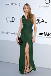 Cara Delevingne arrived at the amfAR Cinema Against AIDS event in a gorgeous green gown and strappy metallic heels.