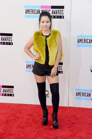 Cierra Ramirez sported a fun red carpet look, consisting of a mustard fur vest and black shorts, at the American Music Awards.