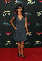Holly Robinson Peete chose a fit-and-flare gray V-neck dress for a fun and flirty red carpet look.