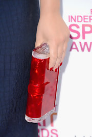 Amy Poehler brightened up her navy dress with a red acrylic, hinged clutch.