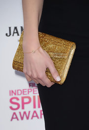 Kira Miro opted for a little sparkle at the Independent Spirit Awards with a gold sparkly clutch.