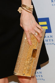 Darby Stanchfield added some sparkle to her black dress with this over-sized, gold clutch.