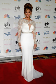 Logan West chose a sleek and stylish white gown with illusion embellished sleeves and a flowing train for her look at the Miss USA Pageant.