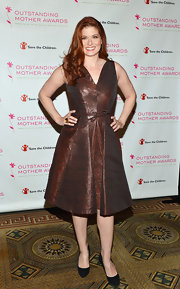 Debra showed off her curves in this metallic brown A-line dress with a pleated skirt.
