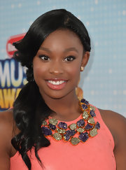 Coco Jones donned a fabulous green and purple statement necklace that served as the perfect contrast to her salmon dress at the Radio Disney Music Awards.