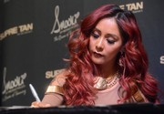 Nicole Polizzi attended the Smart Tan Downtown Convention wearing a statement-making gold tag necklace.