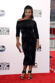 Uzo Aduba added shine to her black outfit with a metallic silver clutch by Lee Savage.
