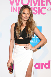 Chrissy Teigen looked ultra modern at the Billboard Women in Music luncheon with this pearlized clutch, crop-top, and high-slit skirt combo.
