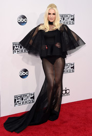 Gwen Stefani unleashed her vampy side at the American Music Awards in a sheer black Yousef Al-Jasmi fishtail gown with voluminous ruffle sleeves.
