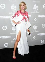 Julie Bowen accessorized with a white and gold box clutch for added elegance.