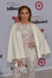 Jennifer Lopez arrived for the Billboard Latin Music Awards wearing a white cape over a lace jumpsuit, both by Zuhair Murad.