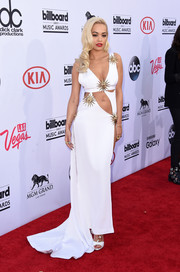 Rita Ora looked ravishing at the Billboard Music Awards in a white Fausto Puglisi cutout gown featuring the brand's signature sun embellishment.
