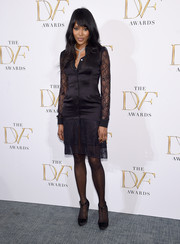 Naomi Campbell polished off her classic ensemble with a pair of black satin T-strap pumps.
