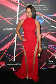 Melanie Brown put on a daring display at the Britannia Awards in a curve-hugging red gown punctuated with see-through panels.